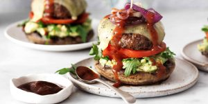 Grilled beef burger on a mushroom bun with avocado and Celebrate Health bbq sauce